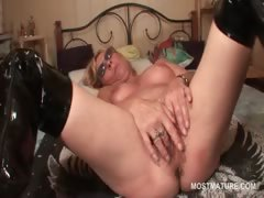 Mature slut in leather boots finger fucking herself in bed